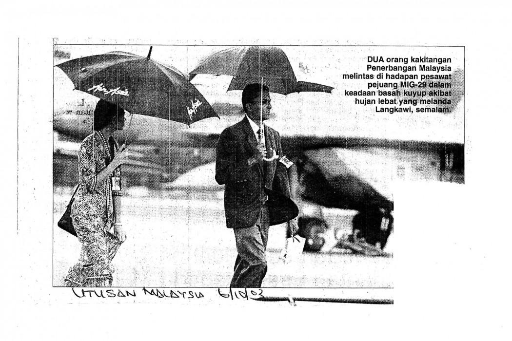 (image) - MAS staff using umbrella with airasia logo